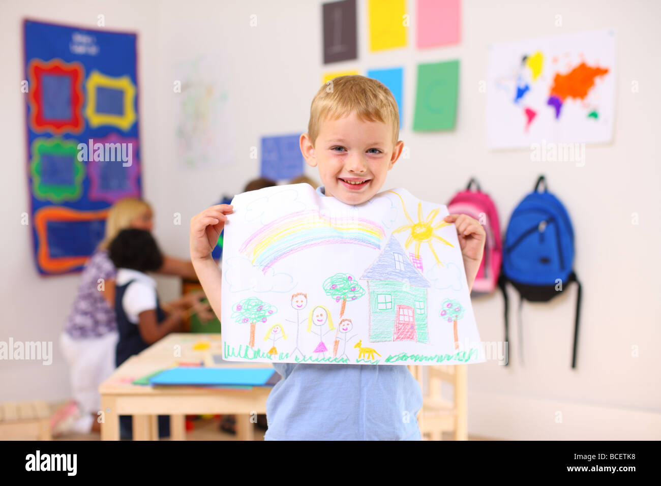 Preschool boy holding up artwork - Stock Image