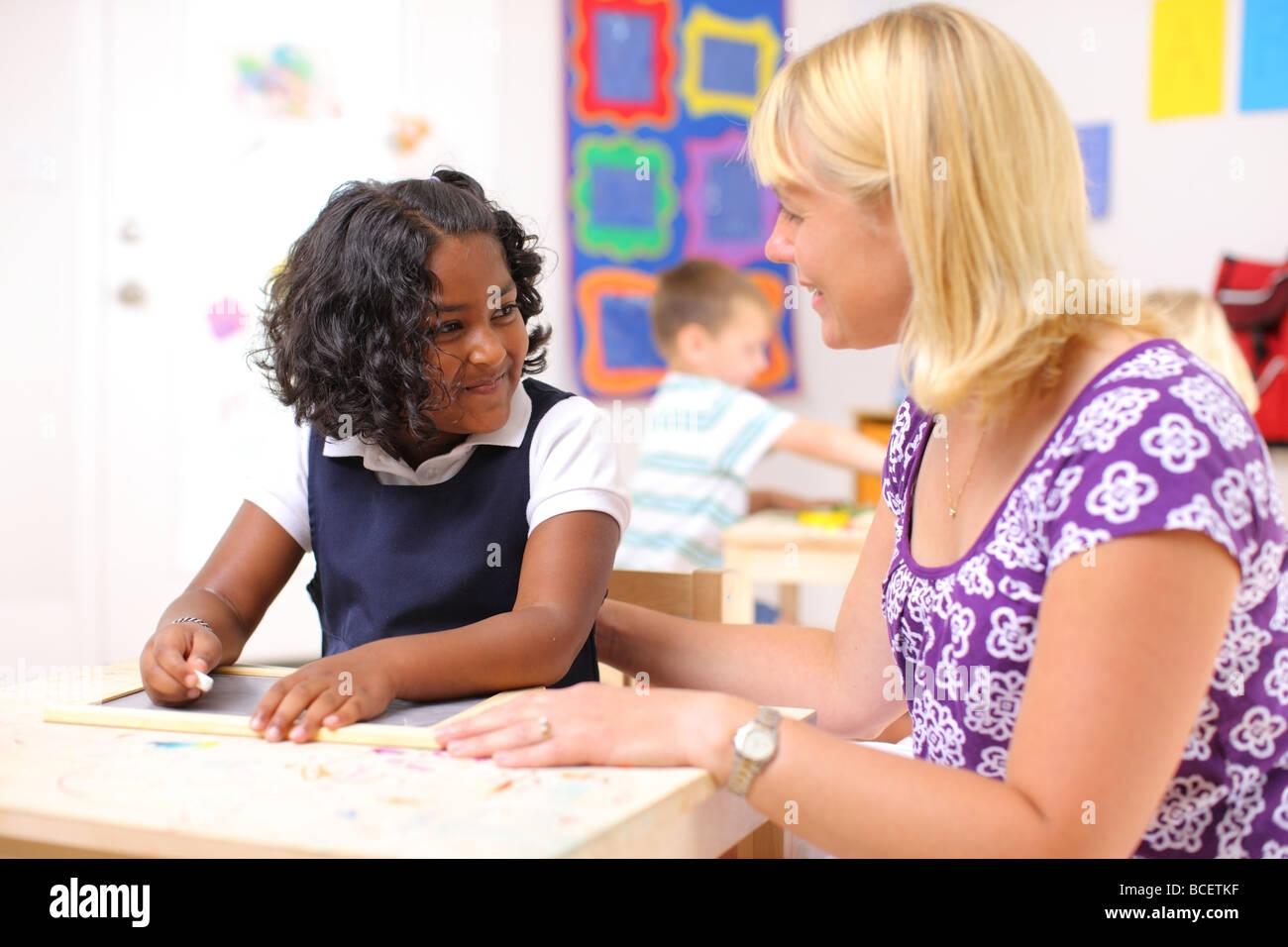 Teacher working with preschool girl - Stock Image