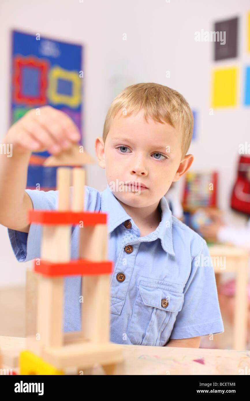 Preschool boy stacking blocks - Stock Image