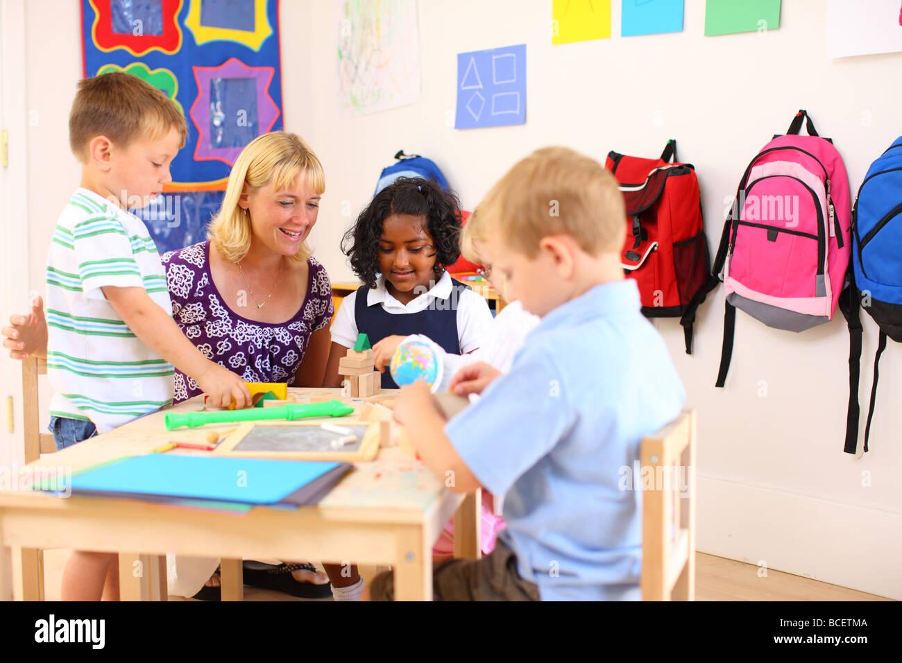 Teacher and kids in preschool classroom - Stock Image