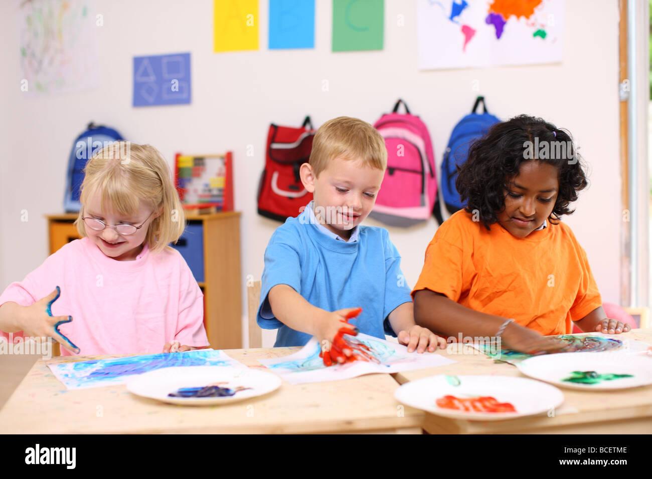 Preschool kids finger painting - Stock Image