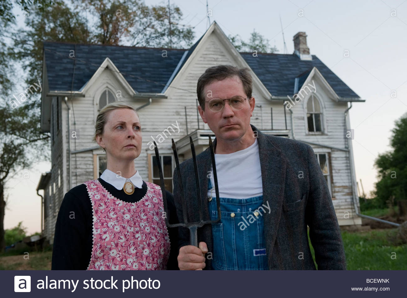 A Husband And Wife Imitate The Painting American Gothic