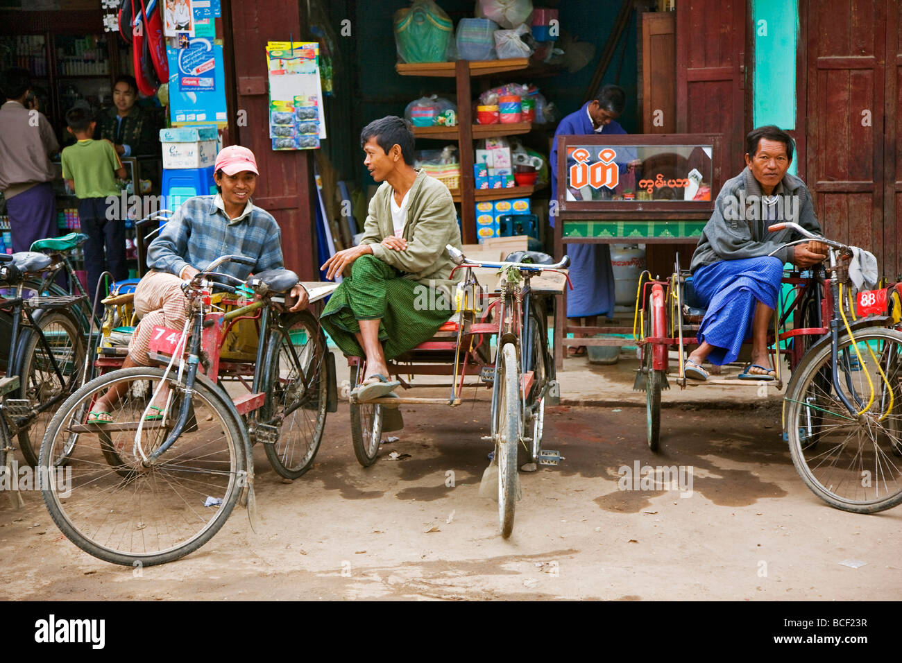 Myanmar. Burma. Nyaung U. The owners of bicycle taxis with sidecars, known as trishaws, relax at Nyaung U market. - Stock Image