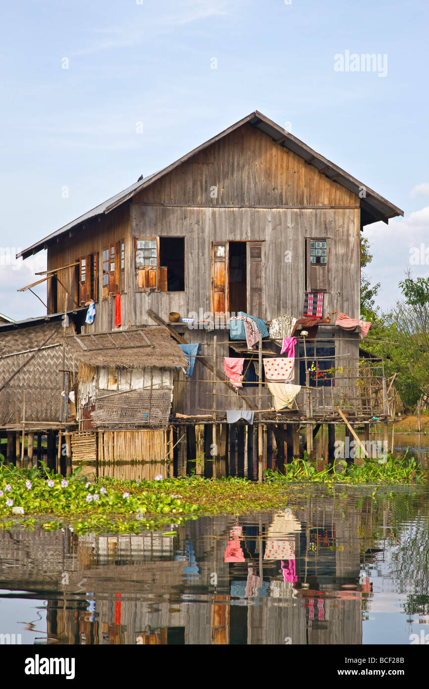 Myanmar, Burma, Lake Inle. A typical Intha wooden house on stilts in Lake Inle, picturesquely sheltered by mountains. - Stock Image