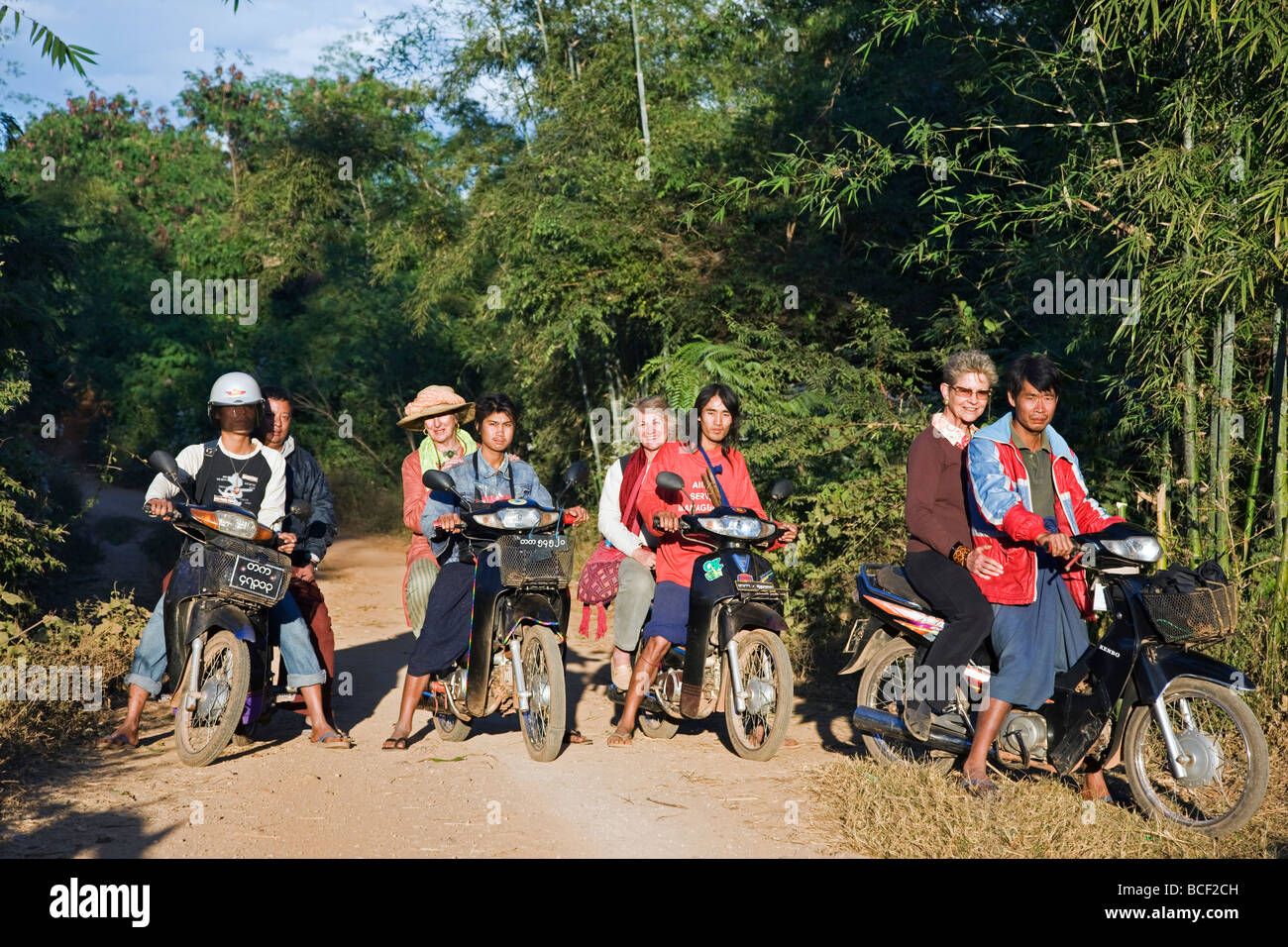 Myanmar, Burma, Lake Inle. A group of tourists ride pillion on rough tracks to visit the Pa-O village of Kya-Toon - Stock Image
