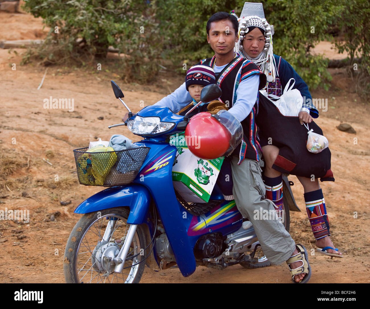 Myanmar, Burma, Namu-op. An Akha family with baggage just manages to ride on one motorcycle near Namu-op village. - Stock Image