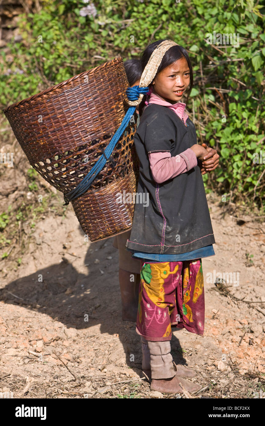 Myanmar, Burma, Wan-seeing.  A young Loi girl carrying a large wicker basket at Wan-seeing village. - Stock Image