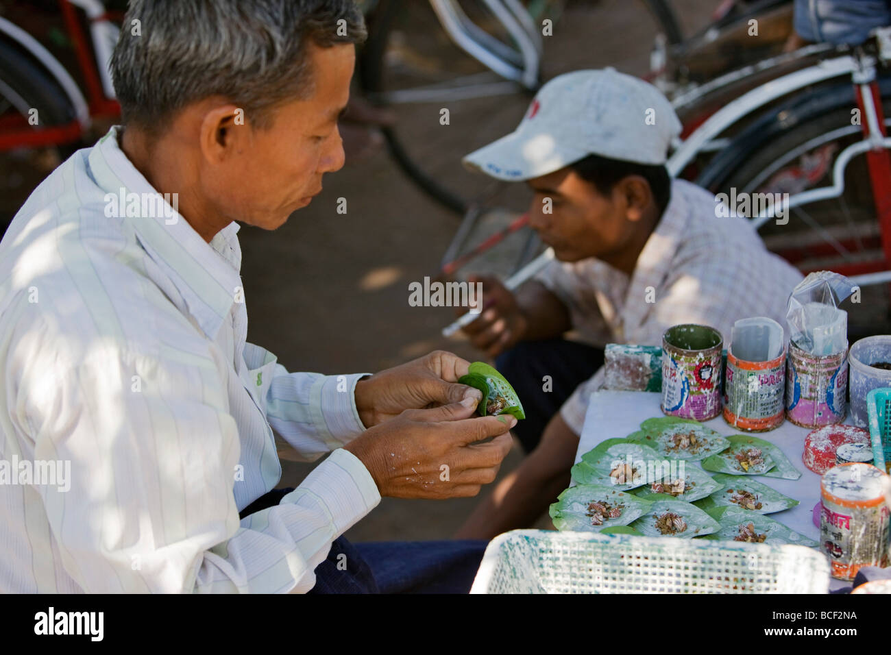 Myanmar, Burma, Yangon. The owner of a small street stall prepares beetle nut wrapped in lime-coated betel leaves. - Stock Image