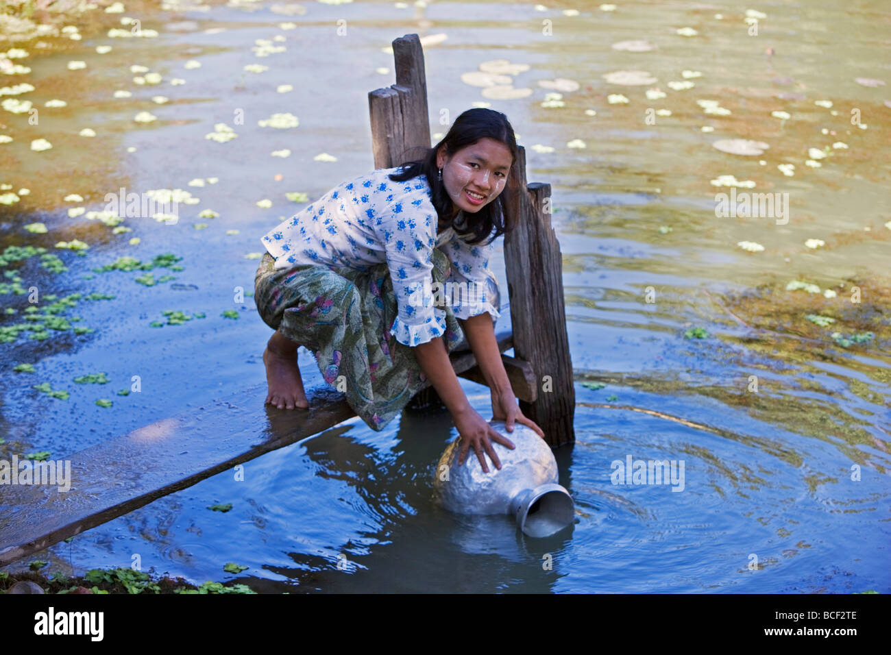 Myanmar, Burma, Mrauk U. A young Rakhine woman draws water in an aluminium pot from a rainwater pond near her village. - Stock Image