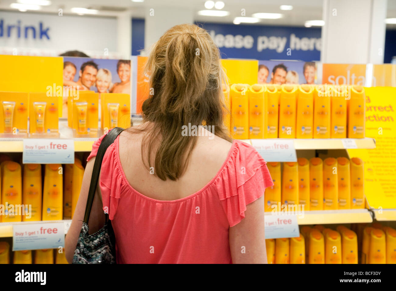 A woman buying sun tan lotion, Boots chemist, North terminal, Gatwick airport, UK - Stock Image