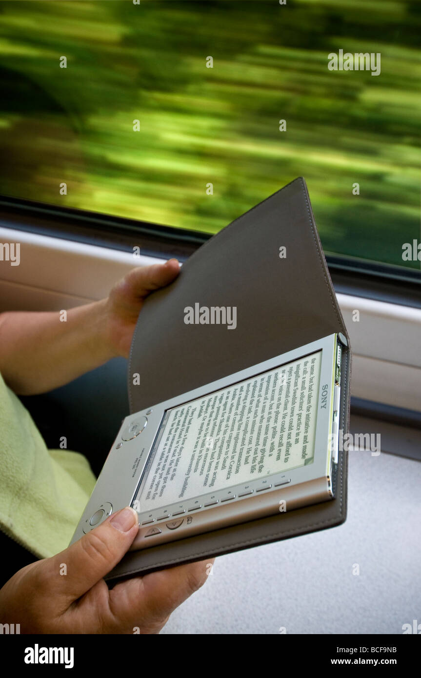 Hands holding Sony eReader portable electronic ebook reading device in train carriage with motion speed blurred - Stock Image