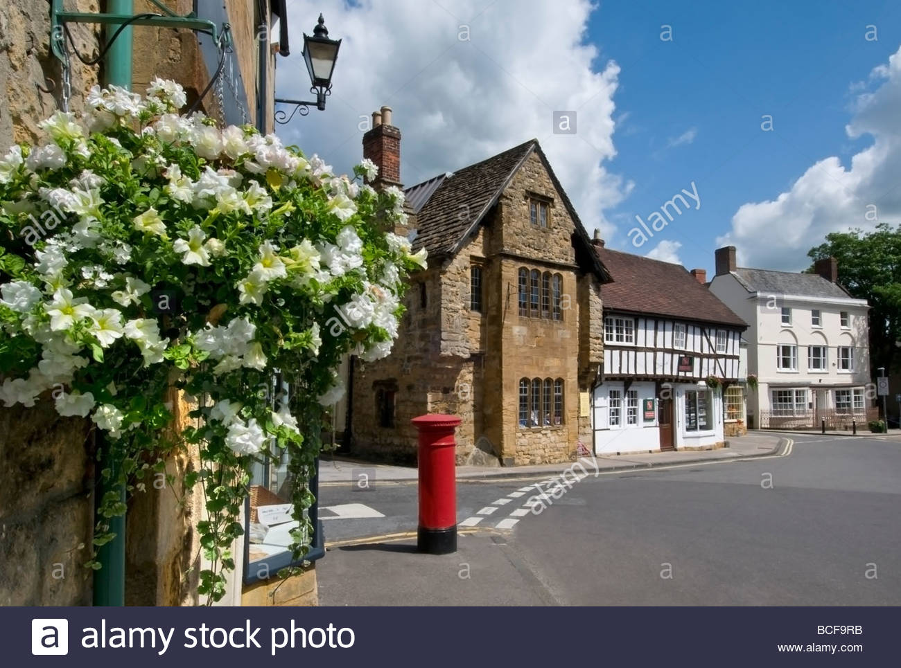 Sherborne historic town centre with hanging baskets of flowers and red post box Dorset  England UK - Stock Image