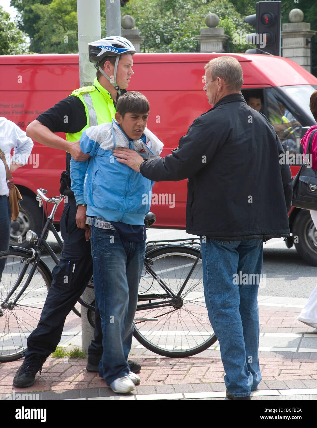 law enforcement officer arresting juvenile - Stock Image