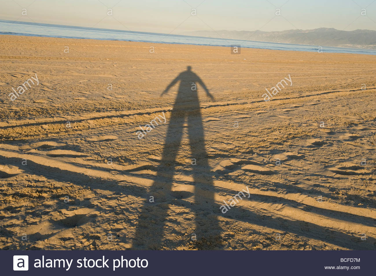 A man's shadow is elongated in Venice Beach, CA. - Stock Image