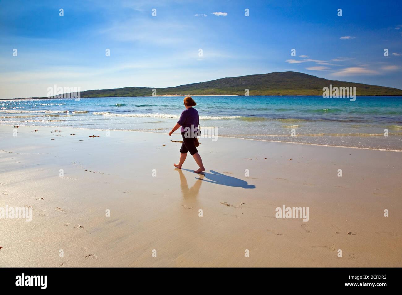 A woman walking accross a sandy beach near Luskentyre Isle of Harris, Outer Hebrides, western isles, Scotland, UK - Stock Image