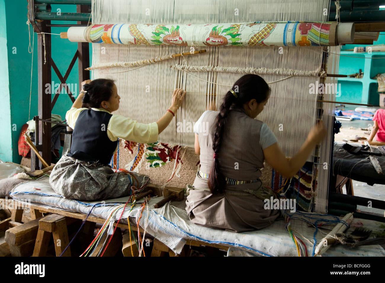Two Women Carpet Weavers Work On A Loom At The Tibetan