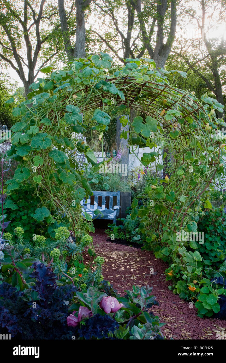 Archway with climbing squash. Pathway scattered with keys to symbolise journey and trials of the homeless. View - Stock Image