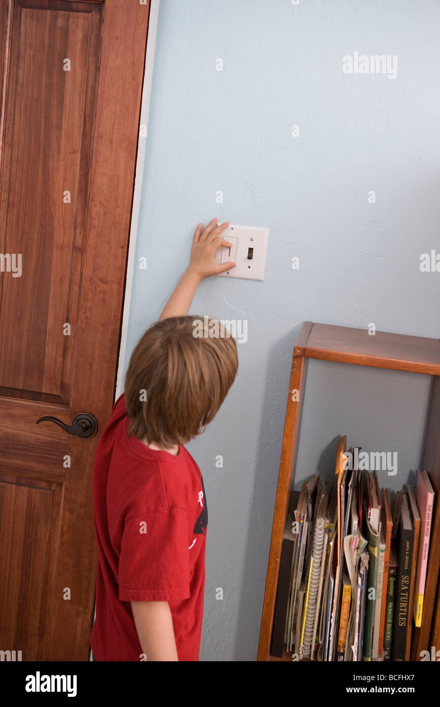 Seven Year Old Boy Turning Off And On Light Switch In His