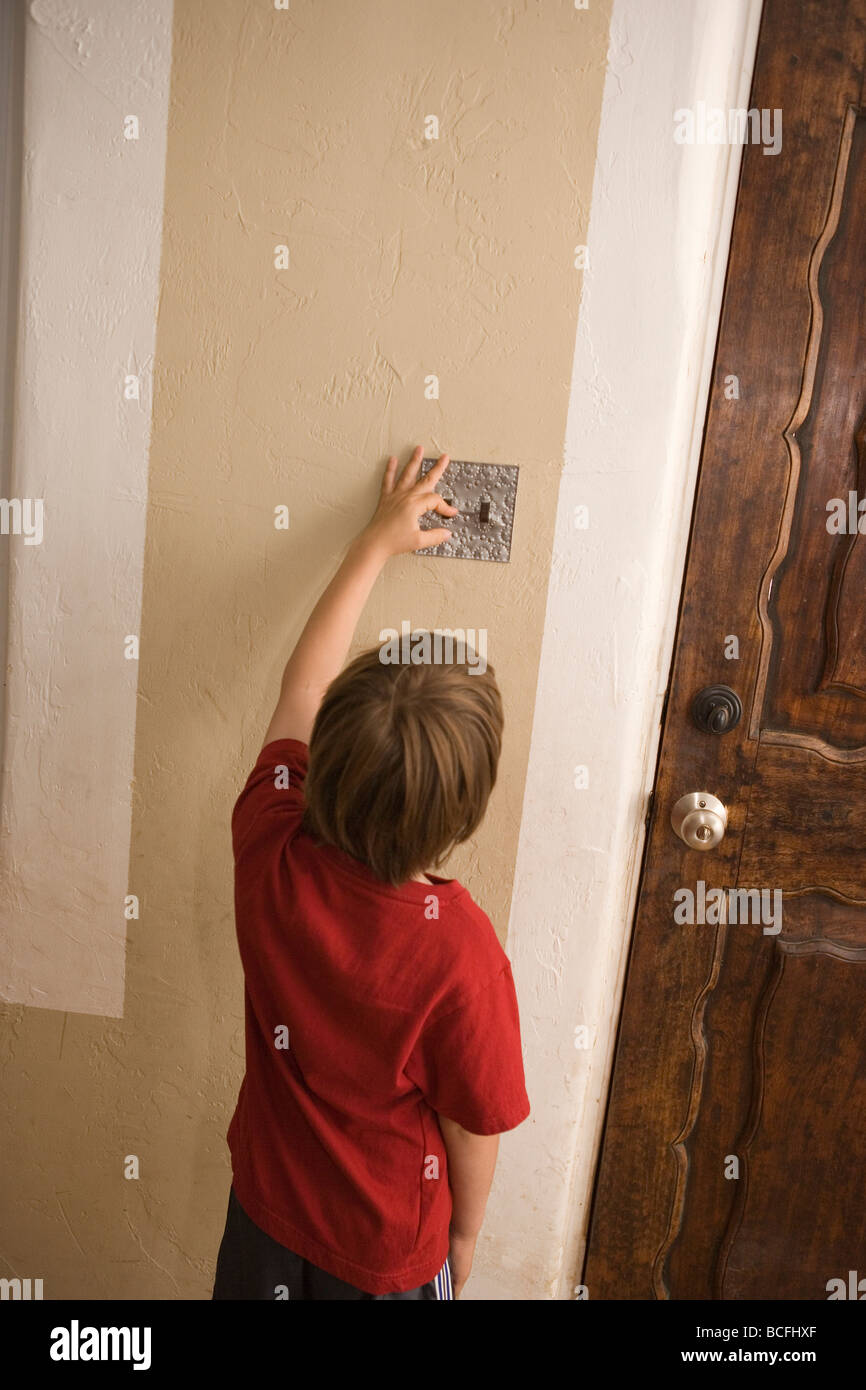 seven year old boy turning off light switch at home to save energy - Stock Image