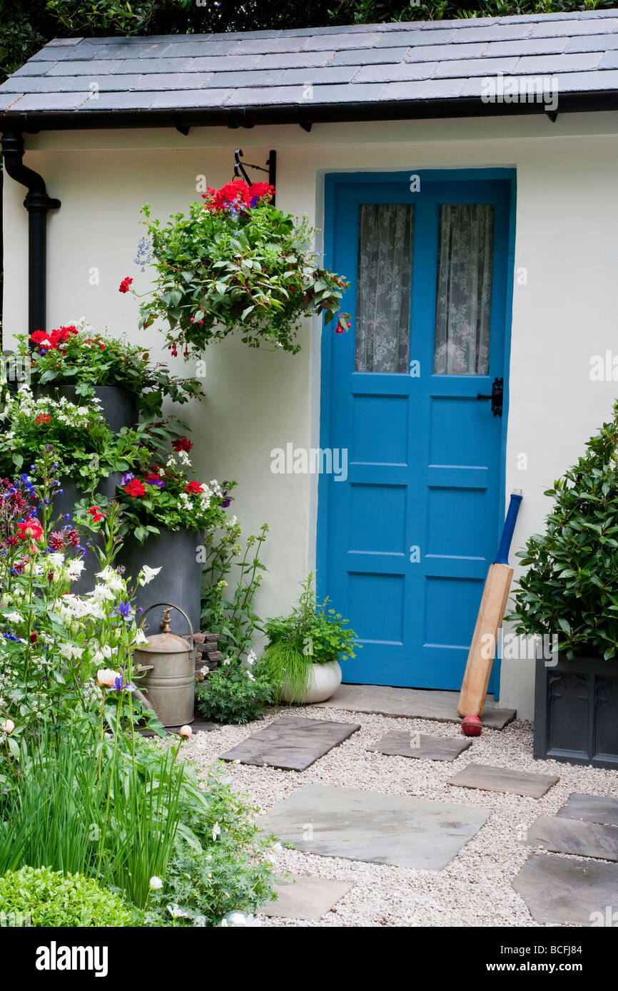 Blue Front Door With Cricket Bat,hanging Basket And Planters.Gravel And  Slate Pathway