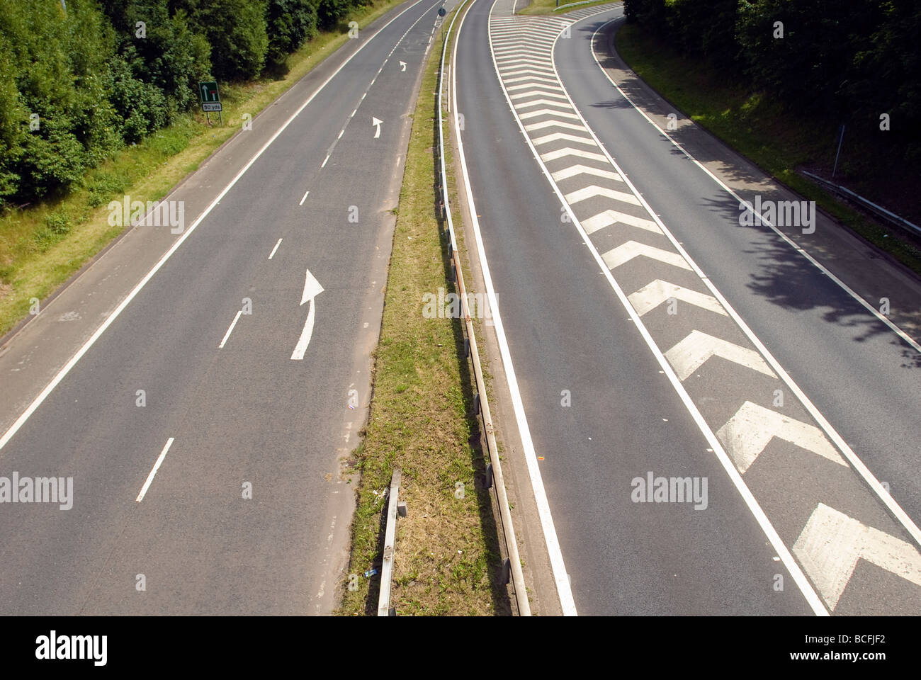 A clear section of dual carriageway road with arrow markings to keep left. - Stock Image