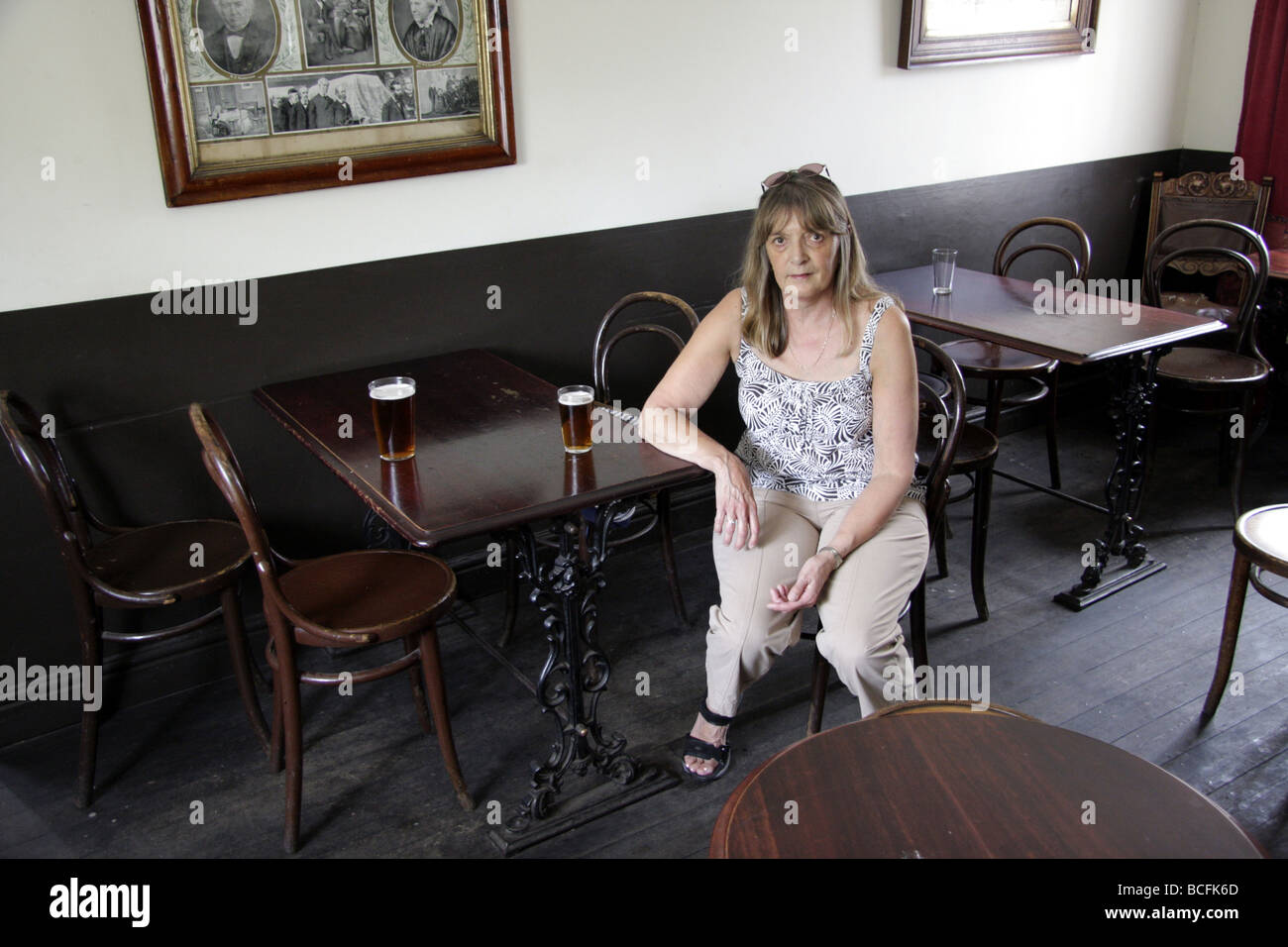 A woman sitting in a very old fashioned pub at the Black Country Museum, near Dudley, West Midlands UK Stock Photo