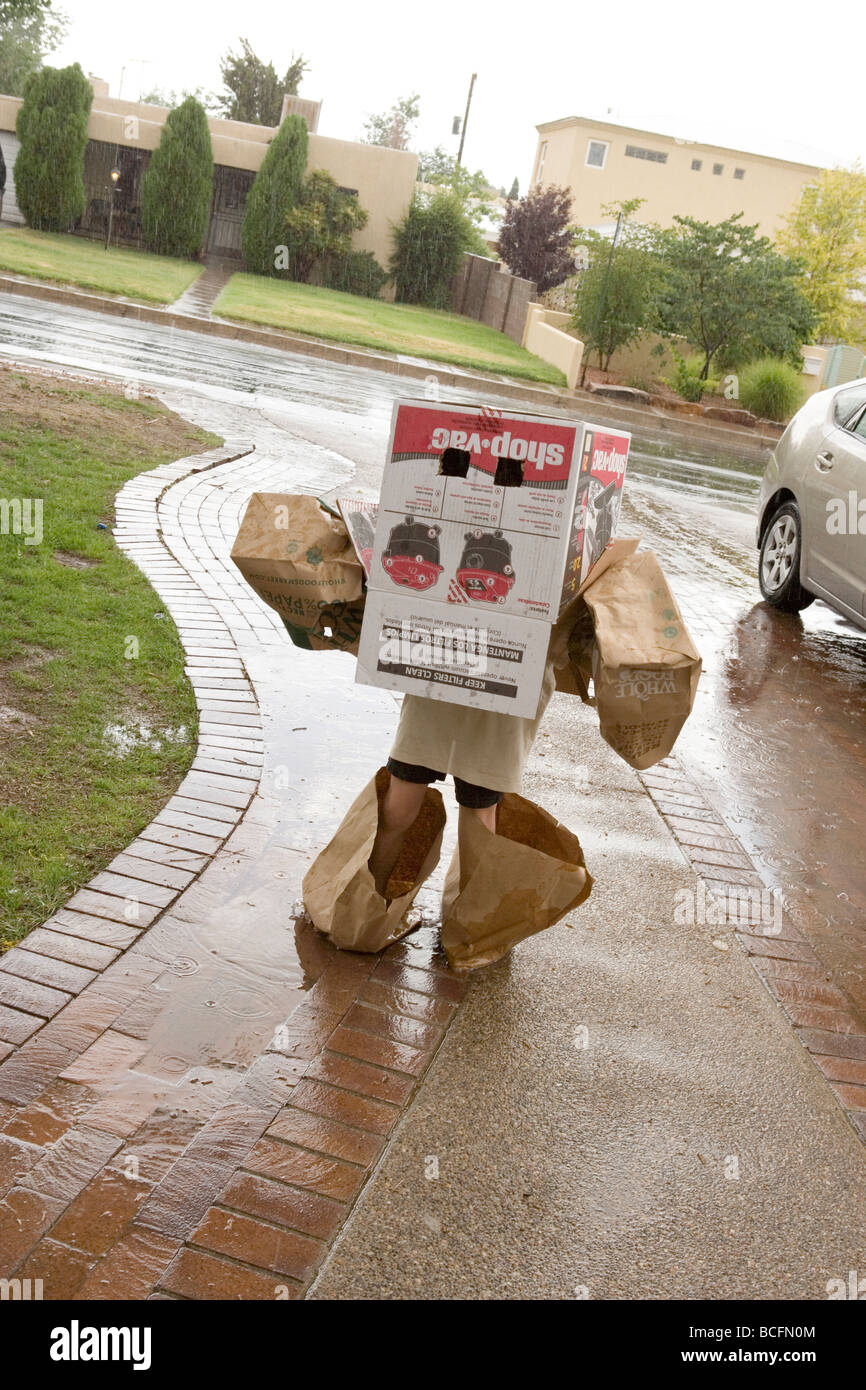 child wearing home made costume of boxes and paper bags, walking in the rain - Stock Image