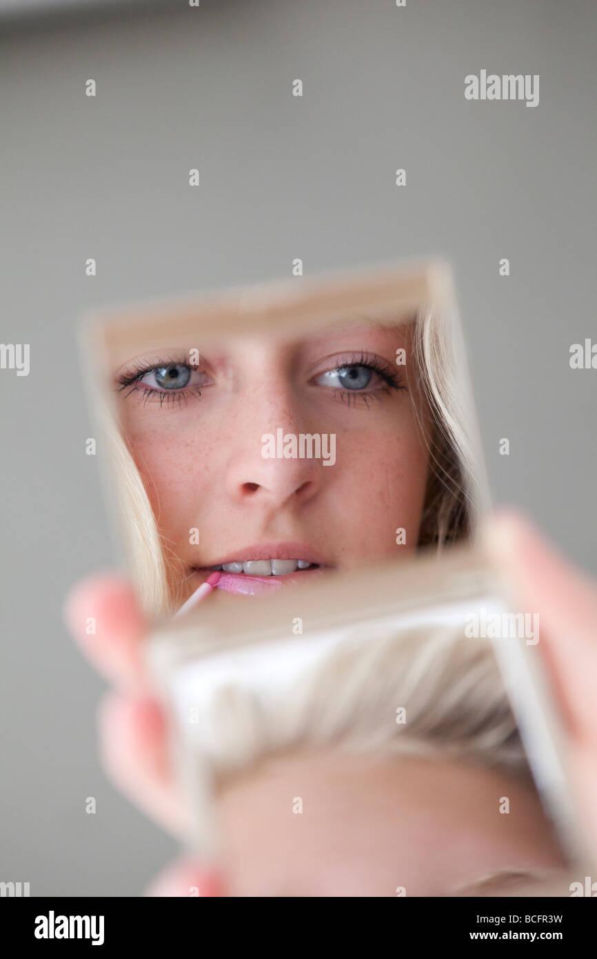 Teenage girl looking in a mirror - Stock Image