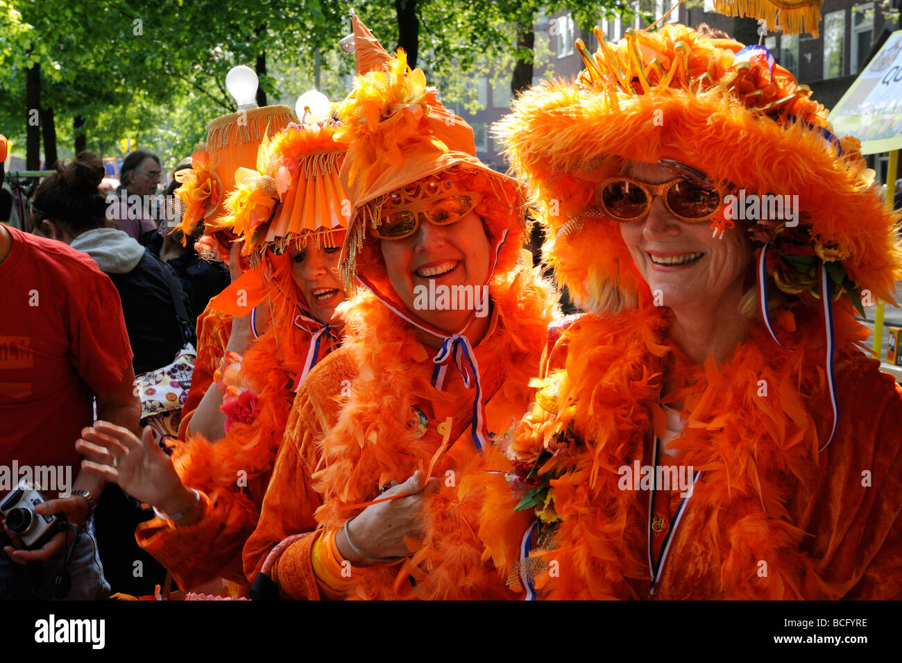 Ladies in orange the royal color at the free market at the 2009 Queen s Birthday celebration - Stock Image