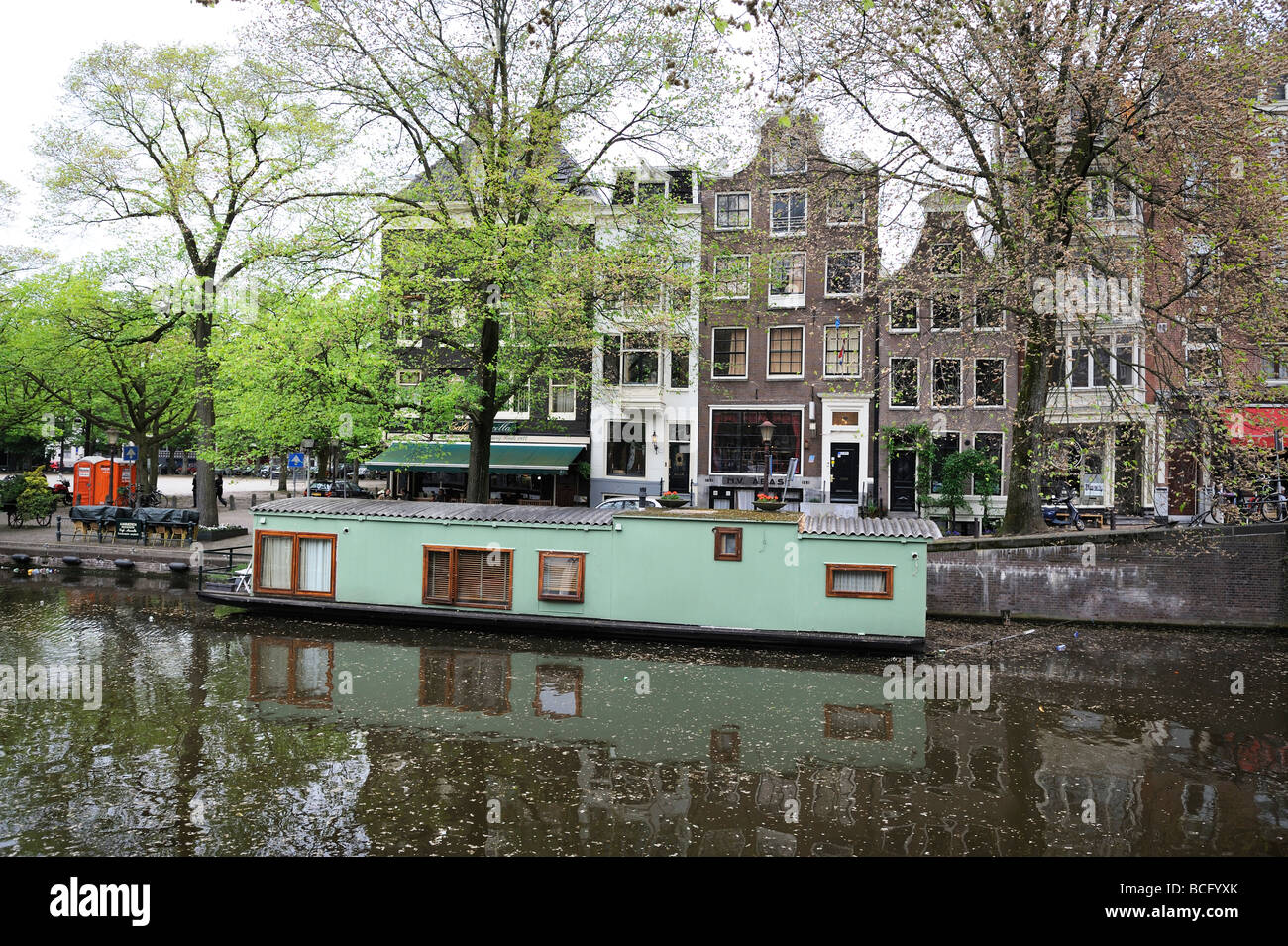 Green house boat opposite cafe Marcella at the Amstelveld in Amsterdam - Stock Image