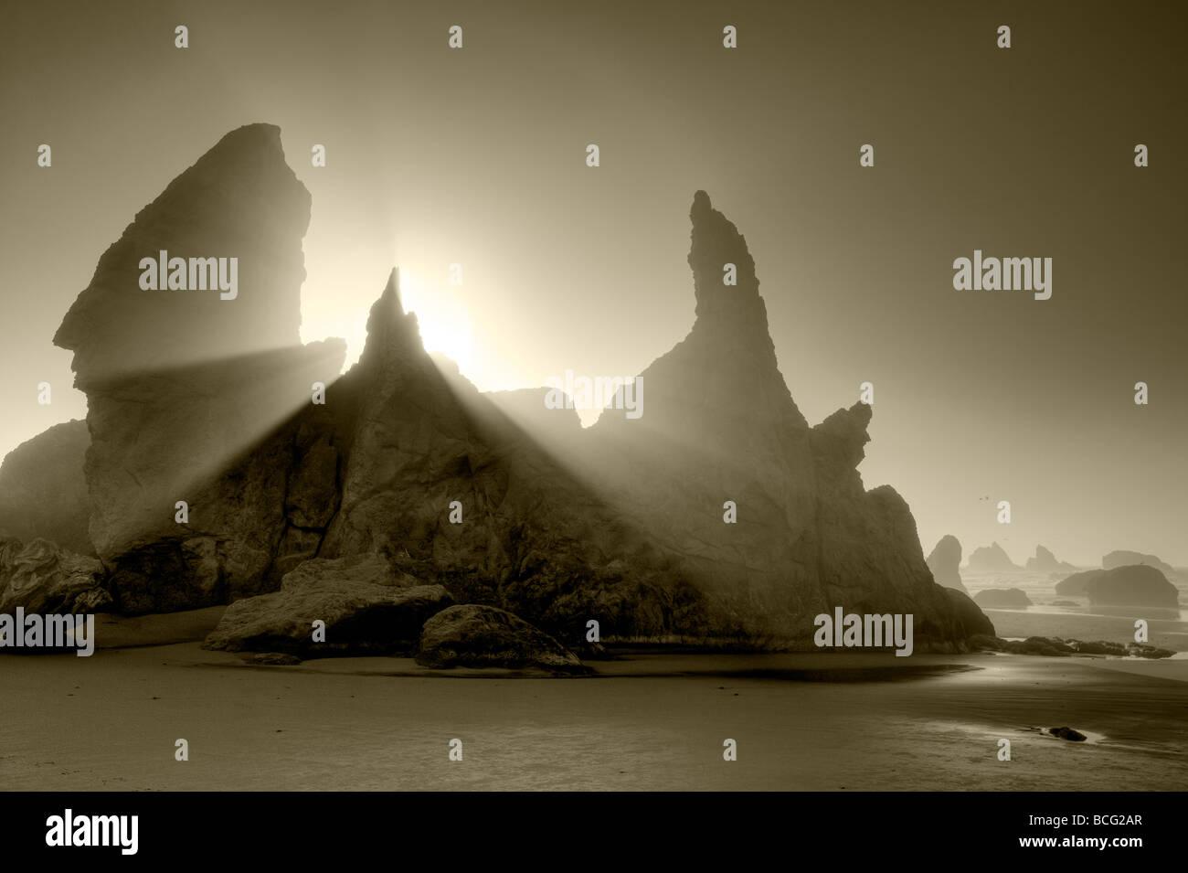 Sea stacks at Bandon Beach with fog and sun rays Oregon - Stock Image