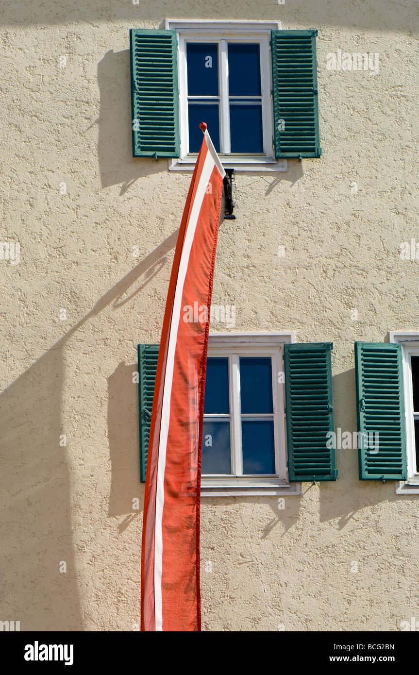 Elongated Austrian flag being flown outside a building with traditional shuttered windows in Zell am See Austria - Stock Image