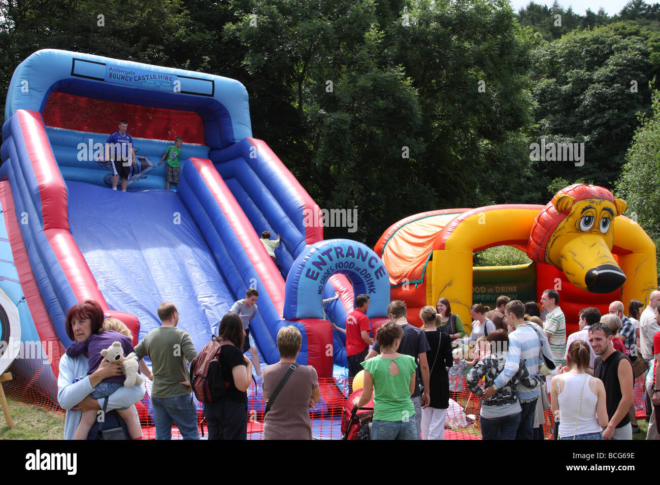 Children on an inflatable slide at an English village show. Ambergate, Derbyshire, England, U.K. - Stock Image