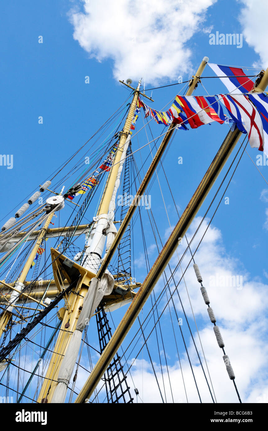 Looking up ships mast with flags rigging shrouds lines and yardarms - Stock Image