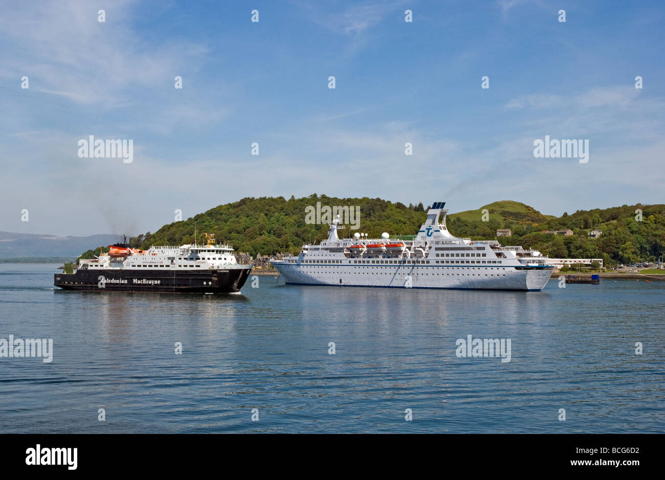 Caledonian MacBrayne car ferry Clansman returning to Oban in Scotland with cruise liner Astor anchored in the harbour Stock Photo