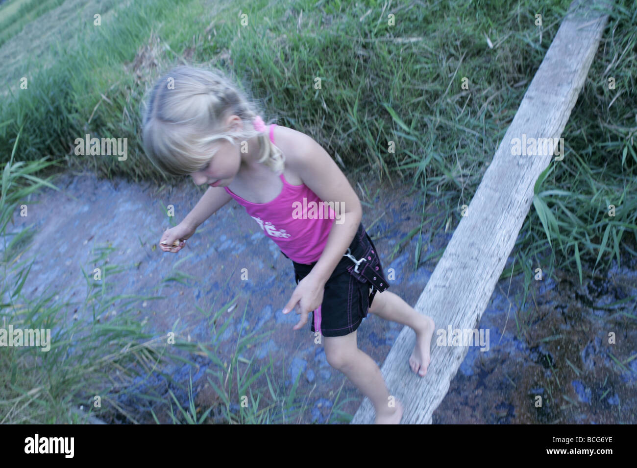 Farmers daughter playing, walk the wooden plank crossing the ditch in balance Stock Photo