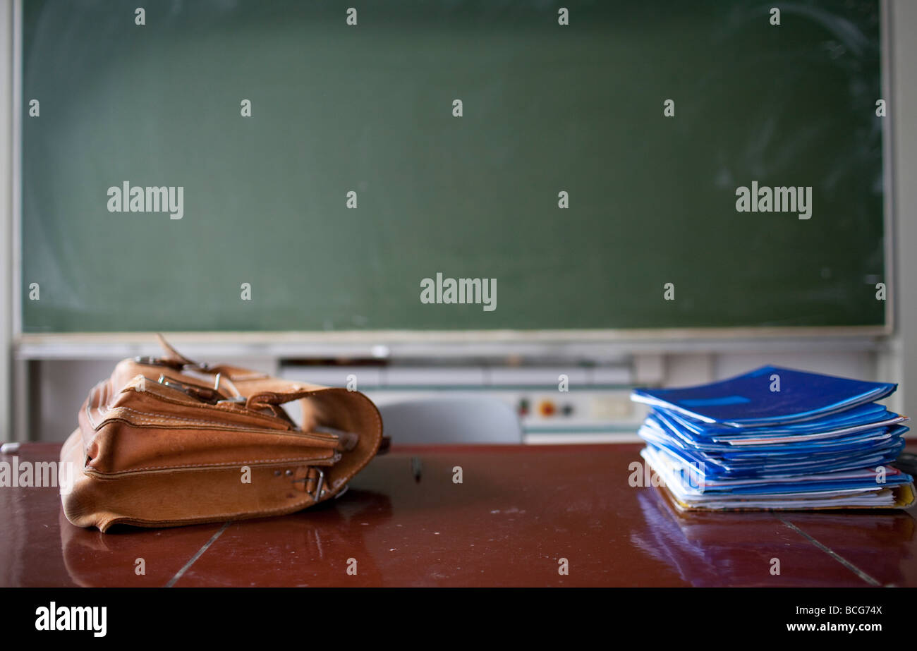 Empty classroom with briefcase and piled up notebooks Stock Photo