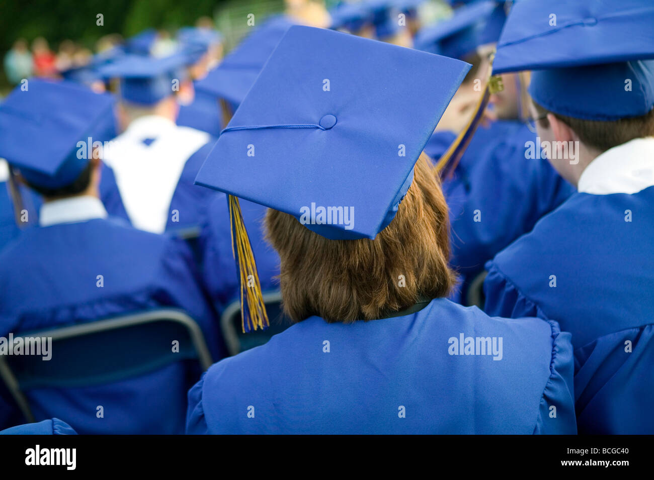 High School students wearing blue and gold cap and gown attend Graduation  Ceremony in USA efab39d529f