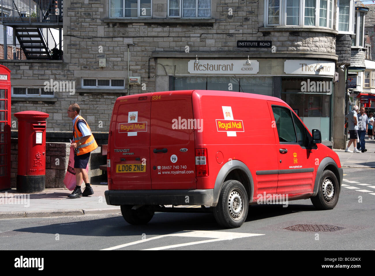 Postman collecting mail from Postbox, ready to load into Postvan - Stock Image