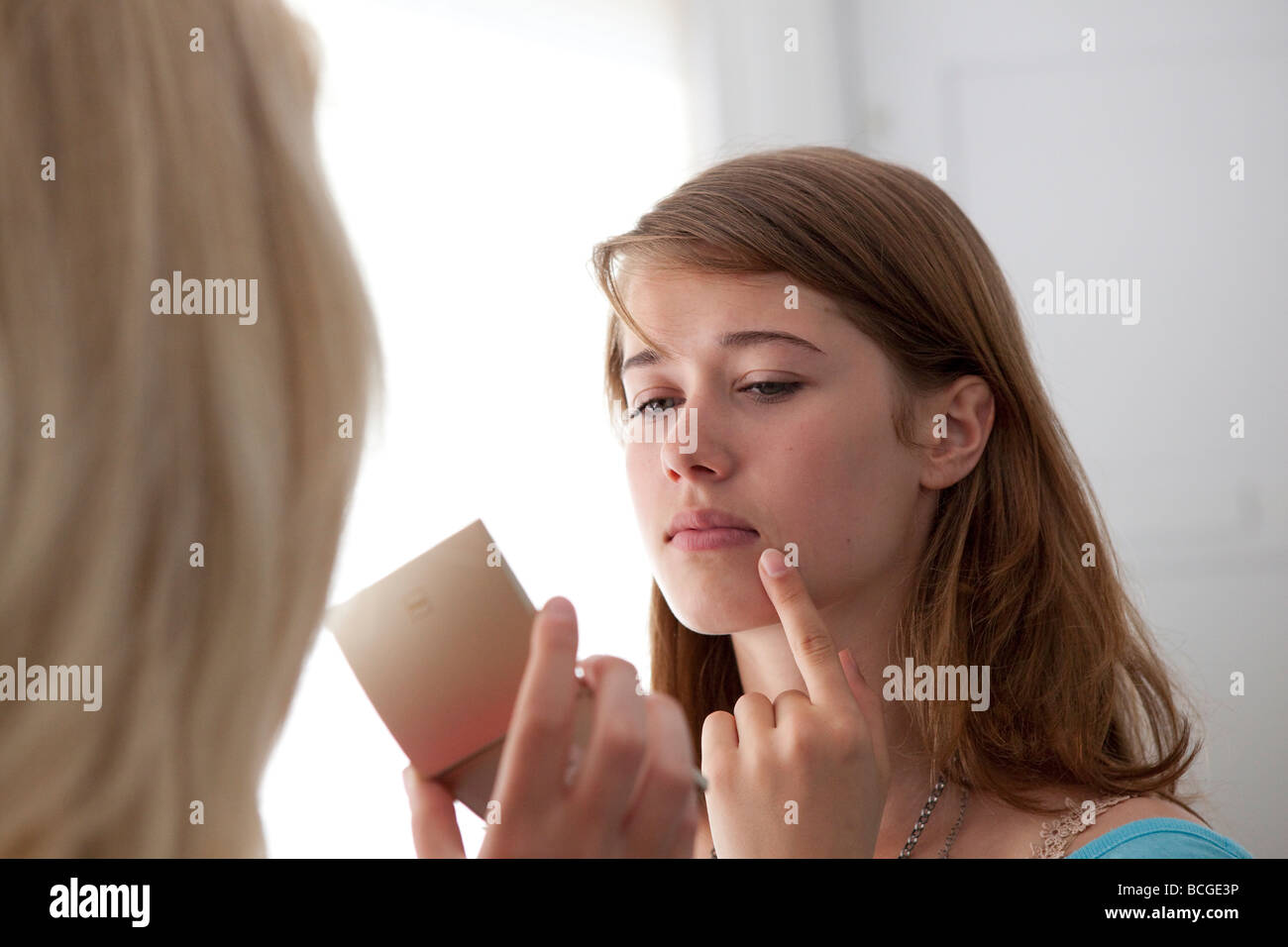 Teenage girl looking in the mirror for pimples - Stock Image