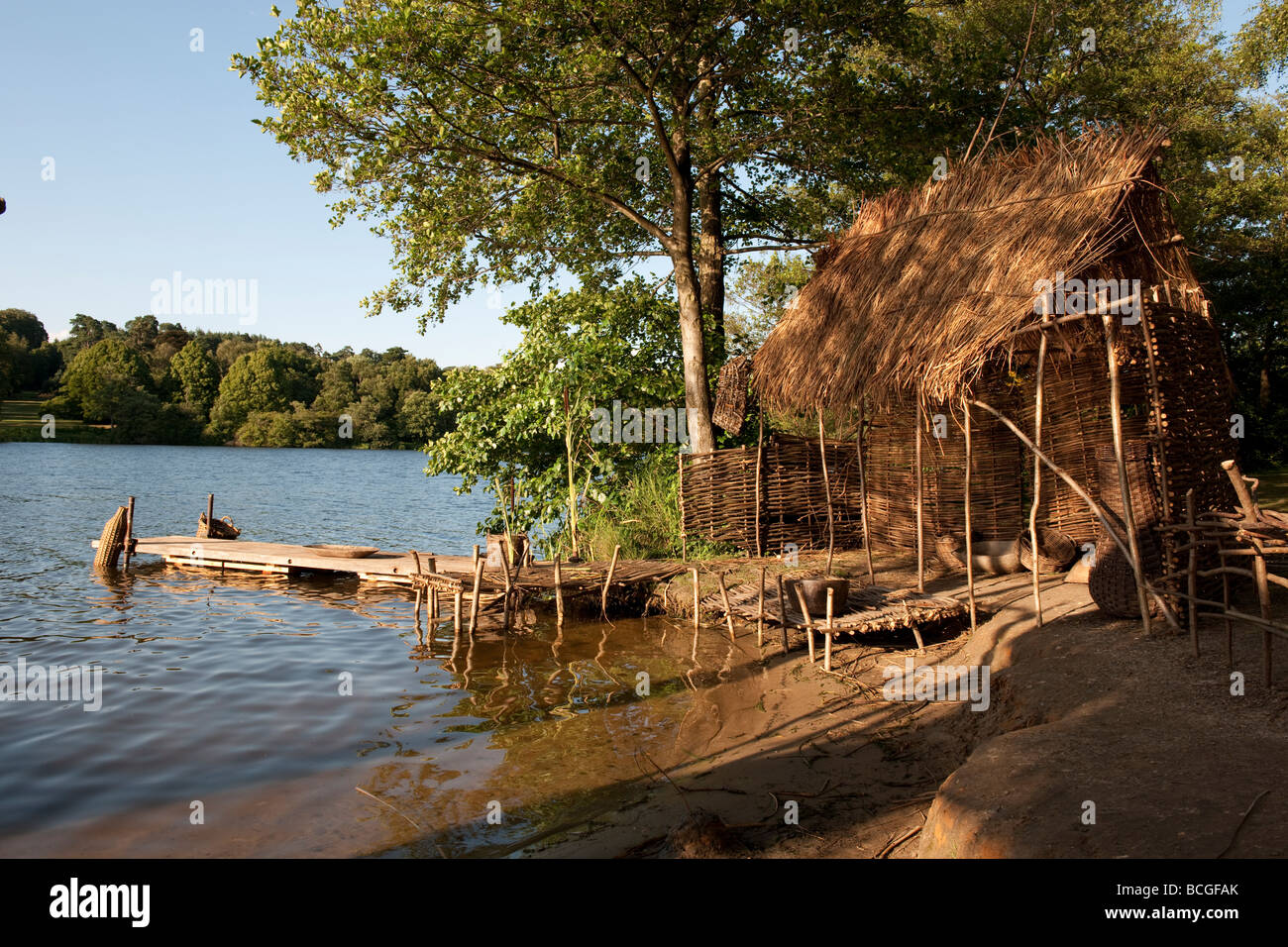 Primative living in stick and reed huts by a lake - Stock Image