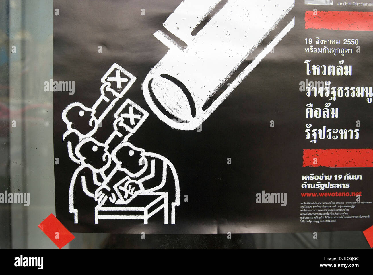 Election poster showing voters casting ballots under the barrell of a gun in Thailand - Stock Image