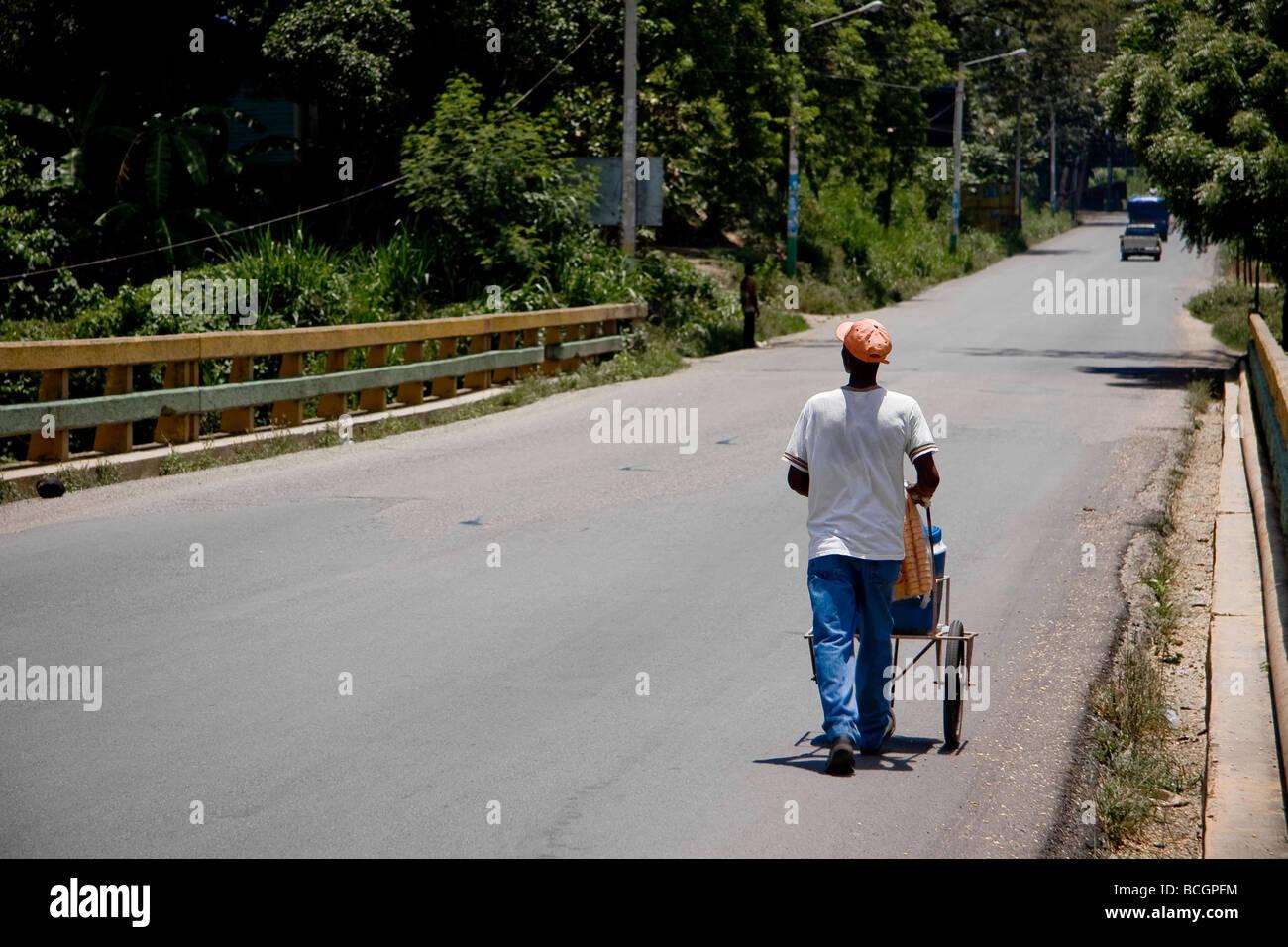 A vendor transports his wares along the road in Santiago Dominican Republic - Stock Image