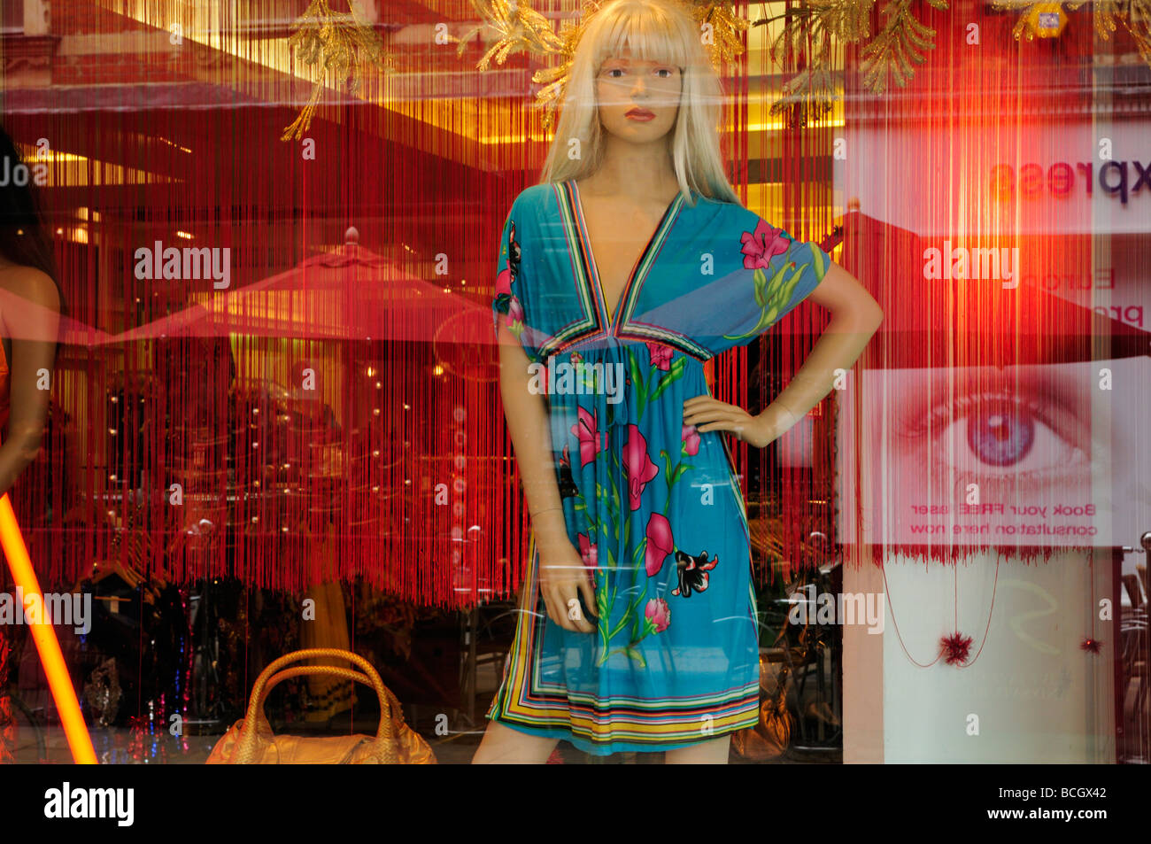 Mannequin and reflections in 'Bukhara' clothes shop window display, Cambridge England UK - Stock Image