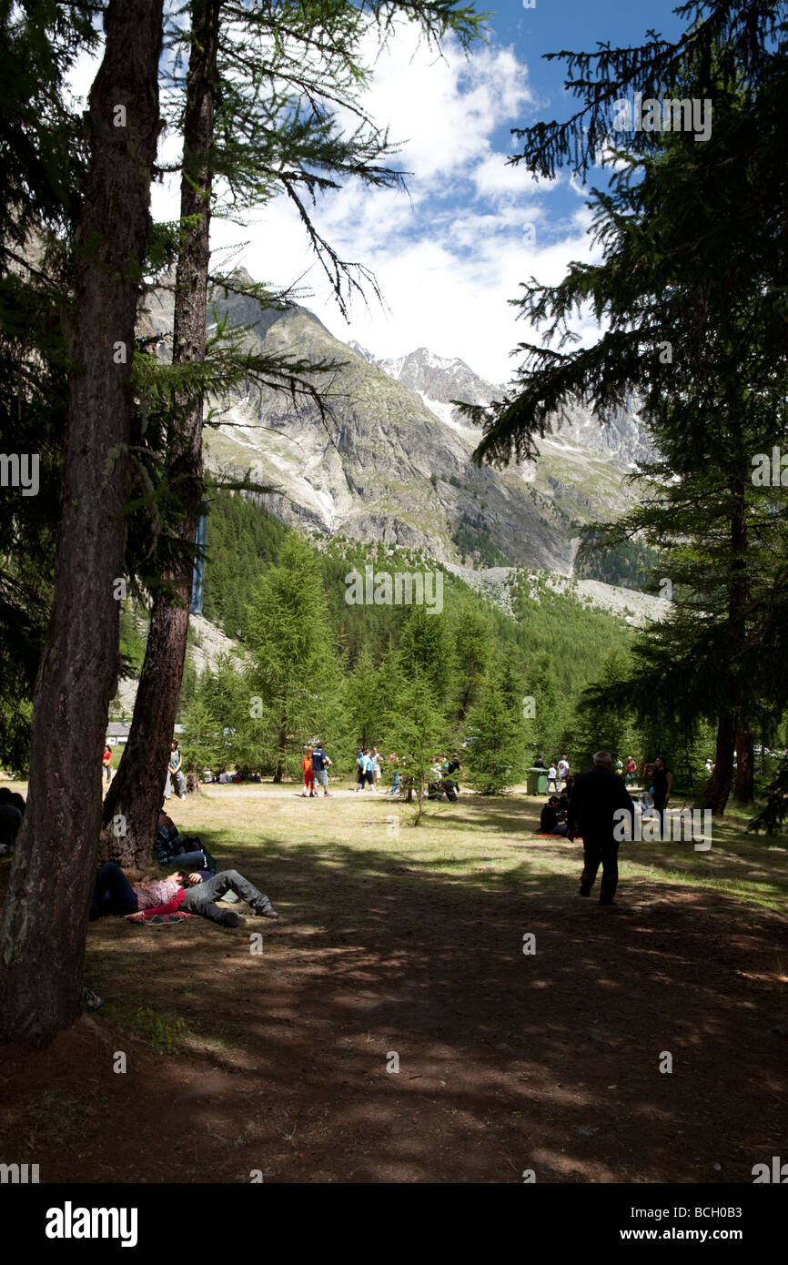 PEOPLE LYING IN THE FOREST WAITING FOR THE CONCERT AT THE CELTICA MUSIC FESTIVAL IN VAL VENY, MONTE BIANCO, VALLE - Stock Image