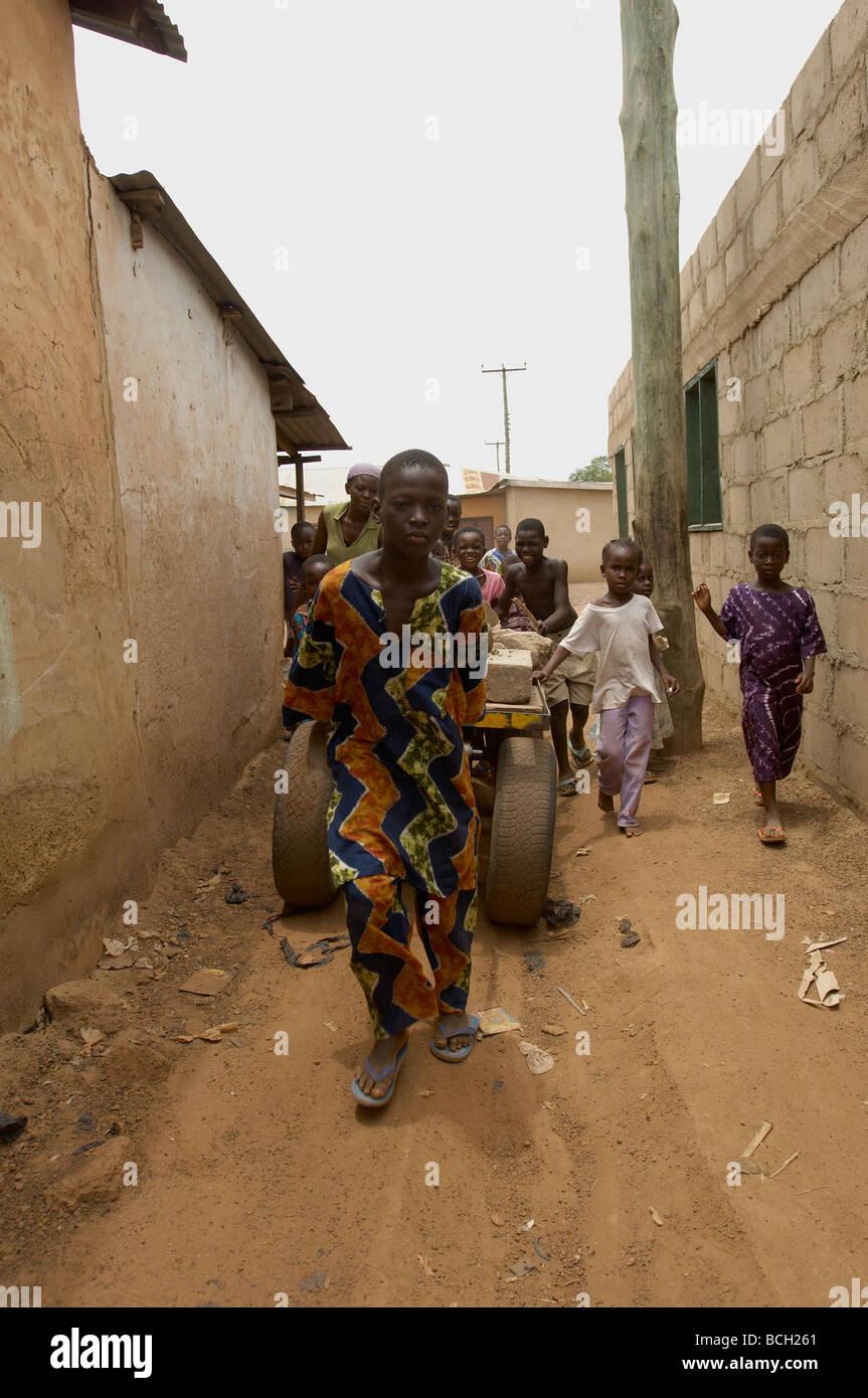 Children pulling heavy cart in Tamale Ghana - Stock Image