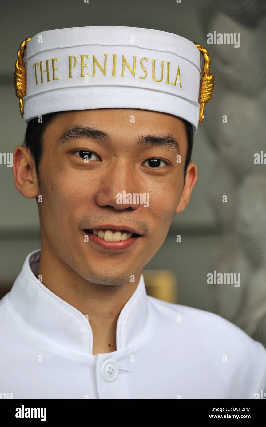 The Peninsula Hotel Hong Kong 5 star luxury hotel doorman smiling Welcome China Asia - Stock Image