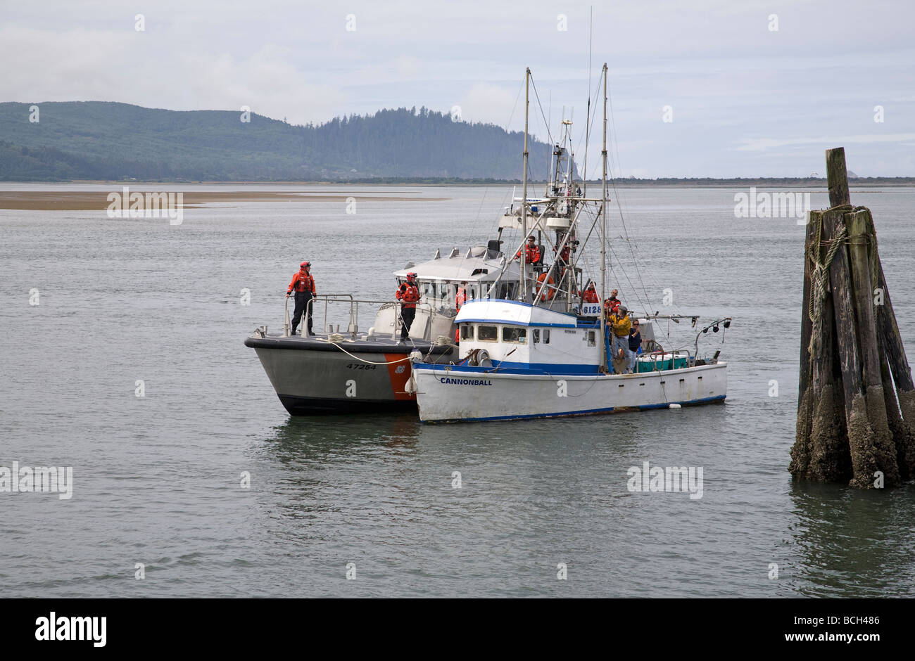 A US coast guard cutter rescues a stranded fishing boat in Tillamook Bay near the town of Garibaldi on the Oregon - Stock Image