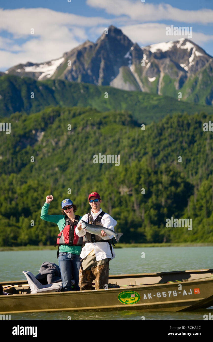 Fisherman holding caught Silver Salmon while standing in a boat on Big River Lakes in Southcentral Alaska during Stock Photo