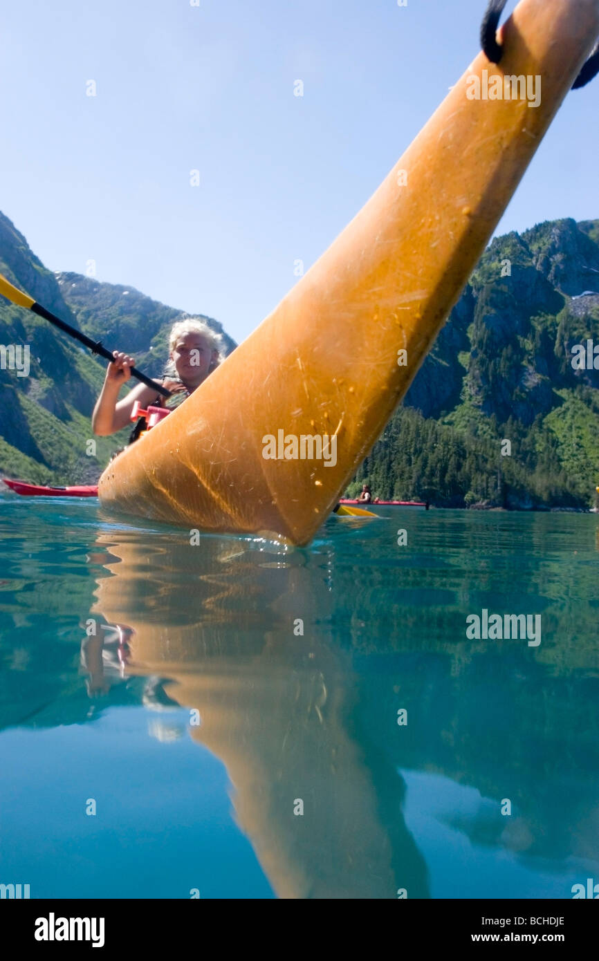 Female kayaker paddles in McMullen Cove on a sunny day in Aialik Bay, Kenai Fjords National Park, Summer - Stock Image